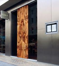 Das Logo und die Eingangstür des Restaurants Roka in London, eine Kombination aus großen Stahltüren und Holzverkleidungen