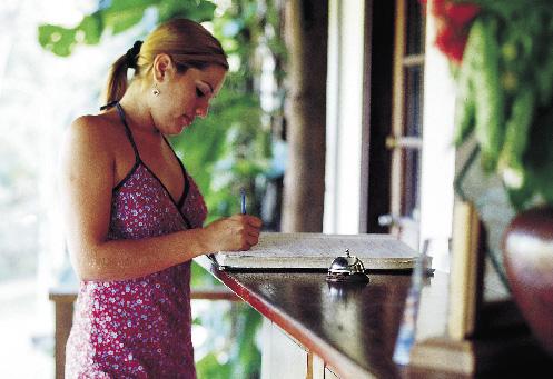 Eine Frau steht an der Rezeption und schreibt einen eintrag ins gästebuch