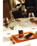 ein klassisch gedeckter Tisch mit Wein und einer kulinarischen Kreation