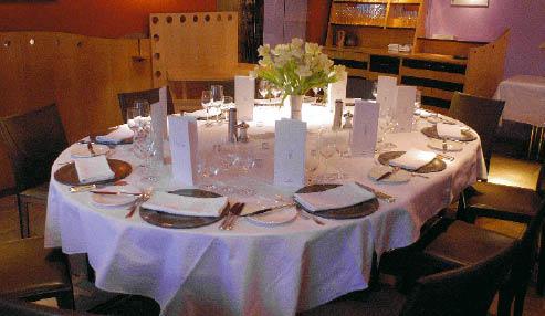 ein ovaler und weiß gedeckter tisch