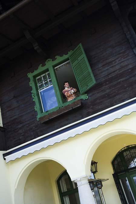 Didi Dorner im Fenster mit verschränkten Armen und buntem Pullover