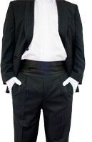 ein Mann im Anzug, Hals bis Knie ist ersichtlich, die Haende in den Hosentaschen