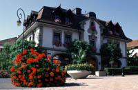 das Restaurant von Philippe Rochat, das ehemalige Rathaus, ein weißes Haus mit einem Brunnen und blühenden Sträuchen