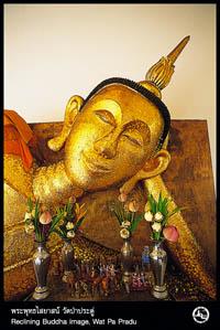 eine liegende Buddha statue mit Opfergaben davor