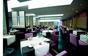 ein modernes Restaurant mit futuristischer Einrichtung, alles in weiss-violetten Farben gehalten