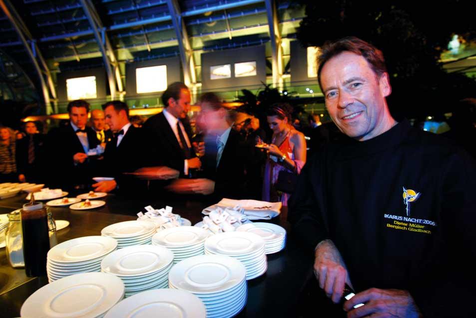 ein Event mit vielen Menschen hinter vielen gestapelten Tellern steht ein Koch