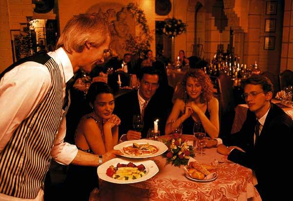 zwei Paare beim Abendessen, während der Kellner die Gerichte serviert