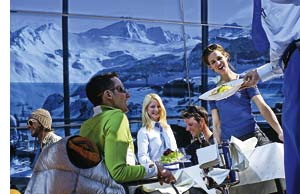 eine Gruppe junger Menschen genießt ihr Mittagessen auf einer Skihütte umschlossen von schneebedeckten Bergen