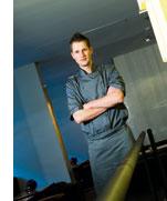 Michael Kempf in grauer Kochuniform und verschraenkten Armen