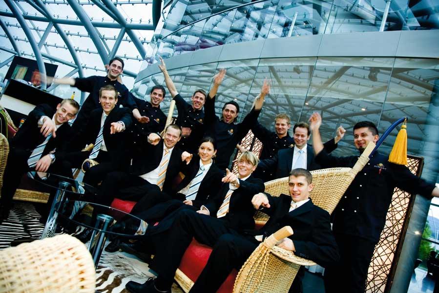 die Crew des Hangar 7 in Anzügen sitzend und lächelnd