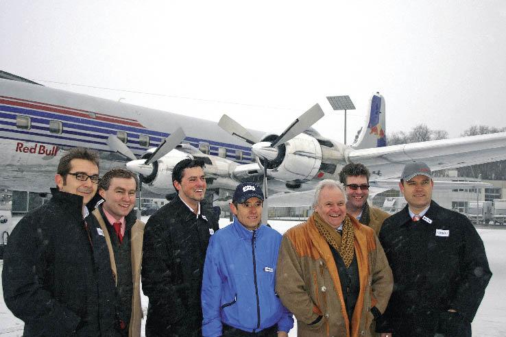 eine Gruppe von Männern stehen am Landeplatz vor einem Flugzeug und posieren für ein Foto