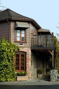 ein idyllisches Haus bestehend aus Backstein mit großen braunen Fenstern