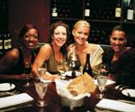 vier fröhliche Frauen beim Abendessen