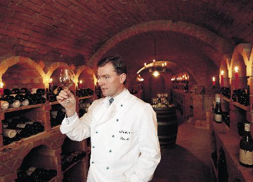 Toni Mörwald mit einem Weinglas im Weinkeller