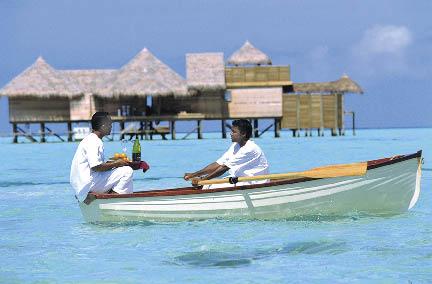 Zwei Einheimische auf einem Holzboot auf den Malediven mit einem Erfrischungsgetränk auf dem Weg zu den Gästen