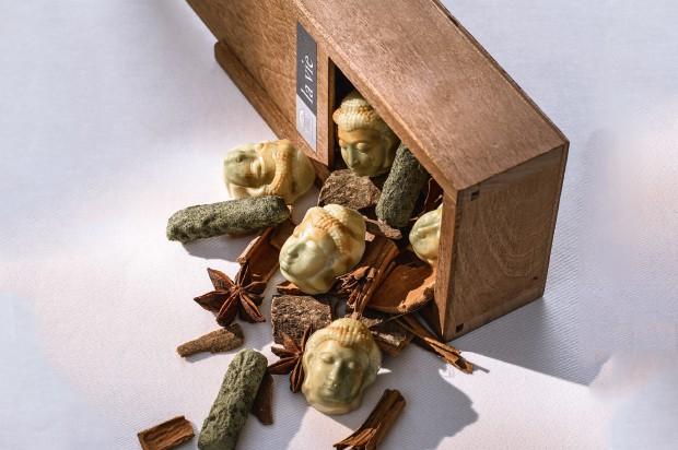Buddhapralinen und petite four in einer Holzschachtel