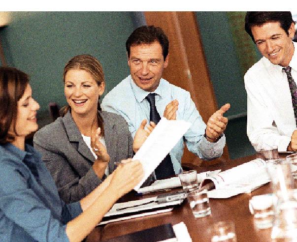 ein geschäftsmeeting ist zu sehen, zwei frauen und zwei herren sitzen an einem konferenztisch,die dame hält notizen in der hand während die anderen drei menschen applaudieren