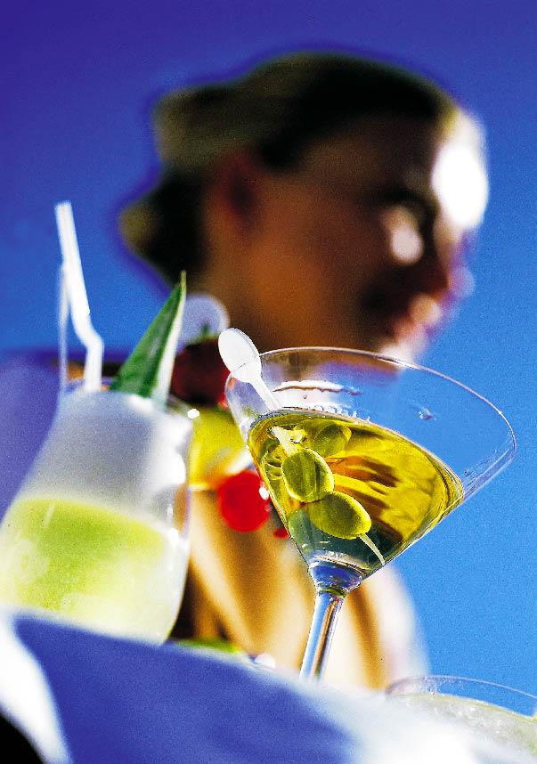 zeigt verschwommen eine Dame und verschiedene Cocktail Sorten, darunter einen Martini