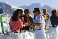 Ein Event in den Bergen ist zu sehen, Menschen genießen die Sonne und Getränke im Alpenraum