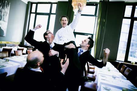 ein Gruppenfoto bestehend aus jubelnden Männern in Anzügen und Kochuniformen