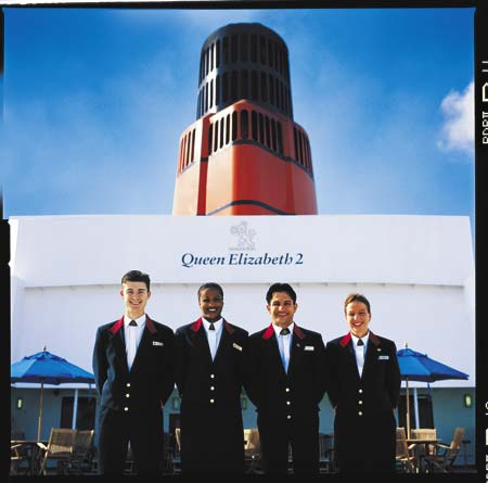 vier Herren des Kreuzfahrtschiffes Queen Elizabeth 2 stehen in Uniform an Deck
