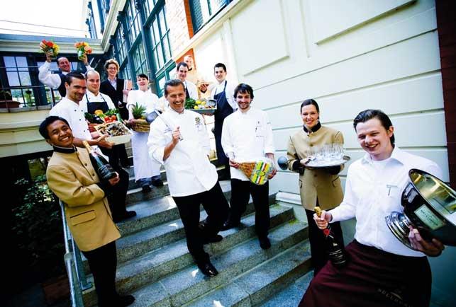 ein Hotelteam auf den Treppen, alle lächelnd mit Blumen und Champagnerflaschen und Serranoschinken