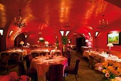 ein Restaurant in einem gewölbten Raum gänzlich in rotem Licht schimmernd