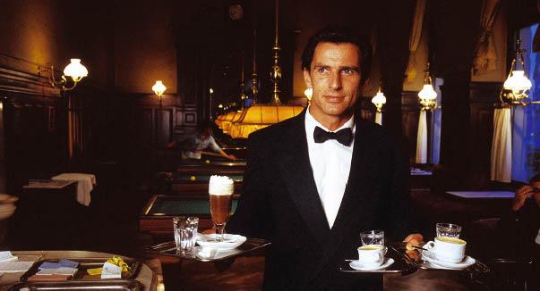 Ein Kellner trägt silbertabletts mit heißgetränken