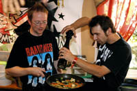 zwei Herren in Ramones T-Shirts würzen ein Pfannengericht