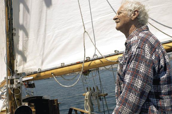 ein Herr im karierten Hemd auf einem Segelschiff