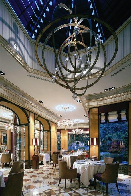 ein endlos hoher Raum mit bodenlangen Fenstern, gedeckten Tischen und einem verspielt modernen Deckenleuchter