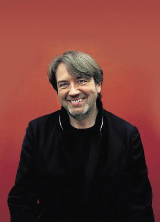 Klaus Kobjoll vor einem roten Hintergrund in schwarzer Kleidung