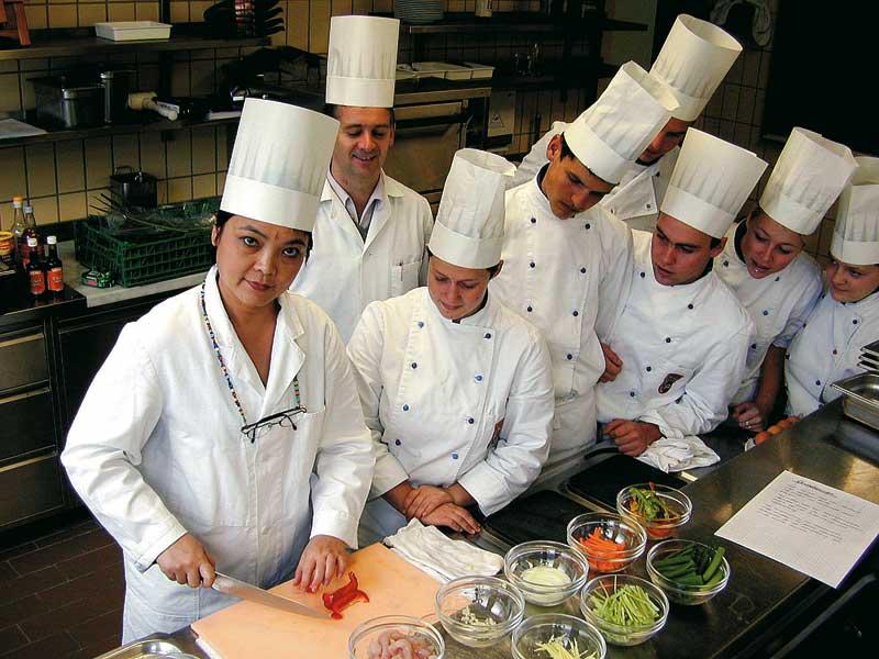 Ein Küchenteam sieht der Küchenchefin eifrig beim Arbeiten zu