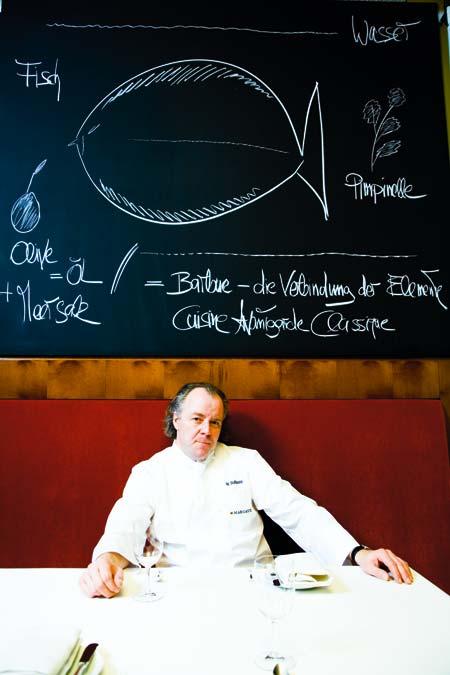 Michael Hoffmann sitzt in seinem Restaurant vor einer gewaltigen Kreidetafel an der Wand