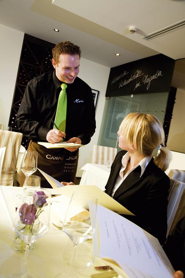 die Servicekraft nimmt die Bestellung einer Dame im Restaurant auf