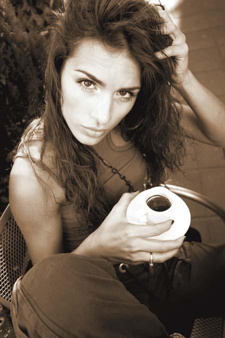 eine Frau hält einen Espresso in der Hand und sieht verschlafen in die Linse