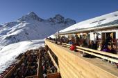 die Terrasse einer Skihütte wo sich Gäste sonnen lassen