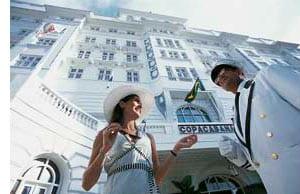 ein Hotelgast unterhält sich mit einem Mitarbeiter vor dem Hotel, Froschperspektive