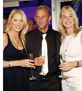 drei prominente persoenlichkeiten, zwei frauen und ein mann posieren zusammen mit sektfloeten gefuellt mit champagner
