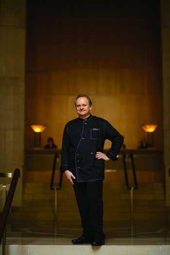 Joel Robuchon stehend in schwarzem Kochgewand mit der Hand in der Hüfte