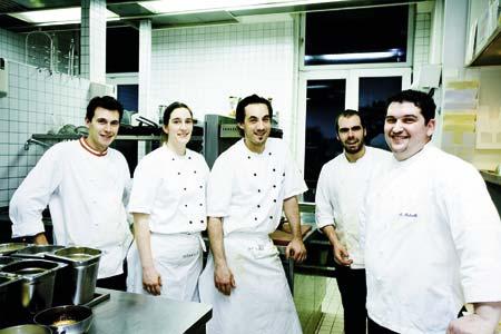 Marco Pedrelli und sein Team gekleidet in weiss und in der Kueche stehend