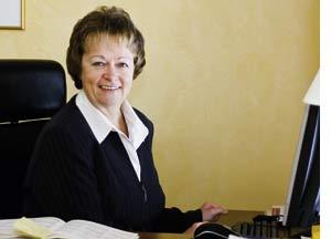 eine ältere Dame an ihrem Schreibtisch, lächelnd in die Kamera