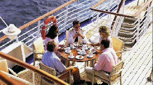 fünf personen geniessen ein gemeinsames essen auf deck eines schiffes