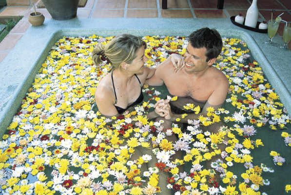Ein paar sitzt in einem von bunten Blumen bedecktem whirlpool