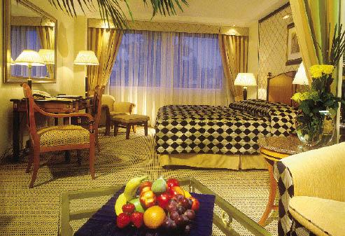 eine Suite im Kempinski, Ein Kingsize Bett vor einem Panorama Fenster, ein Schreibtisch in massiven Holz mit dem dazugehörigen Stühlen und ein Obstkorb auf dem Beistelltisch sind zu sehen