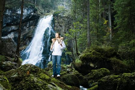 Andreas Döllerer mit einem Reh um den Hals vor einem Wasserfall