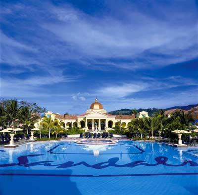 ein großer Pool mit der dazu gehörigen tropischen Hotelanlage ist zu sehen welche von Palmen umrandet ist