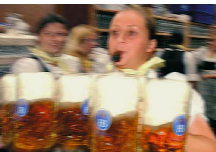 Eine Kellnerin des Oktoberfestes trägt soviele Maßkrüge gefüllt mit bier wie möglich