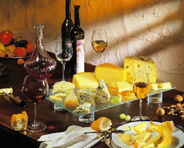Wein, eine Käseplatte und Weintrauben auf einem Tisch