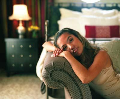 eine junge frau lehnt auf der armlehne einer couch und sieht verträumt in die kamera